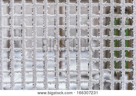 Squared cells of a metallic wire fence completely covered with frost during a cold winter with subzero temperatures