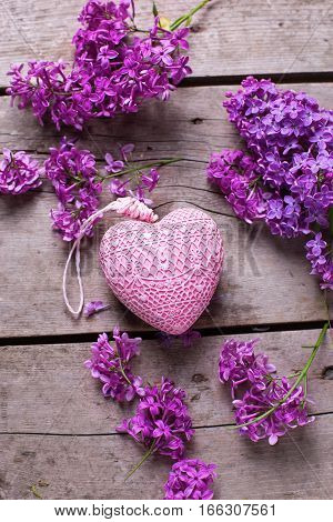 Decorative pink heart and violet lilac flowers on aged wooden planks. Selective focus. Flat lay. Top view.