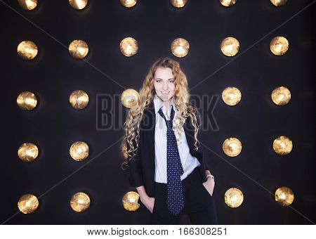Blond happy woman wearing classical suit over golden shining background