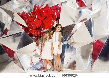 Happy children with balloons at mirror wall