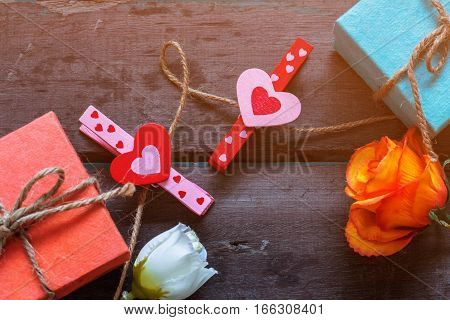 Gift boxes and hearts on old wood.