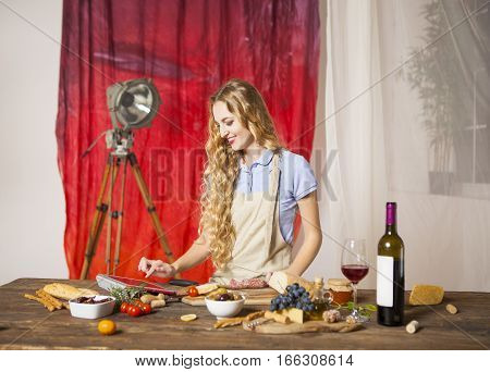 Happy blond woman cooking at the kitchen using tablet computer