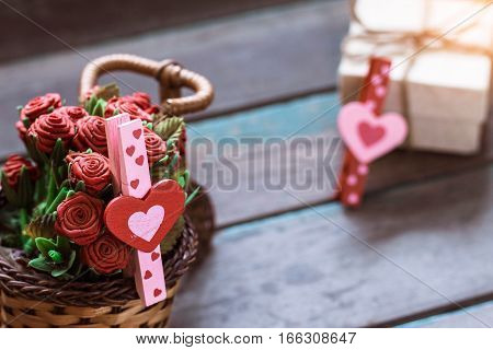 Heart on a basket of roses with old wooden floors.