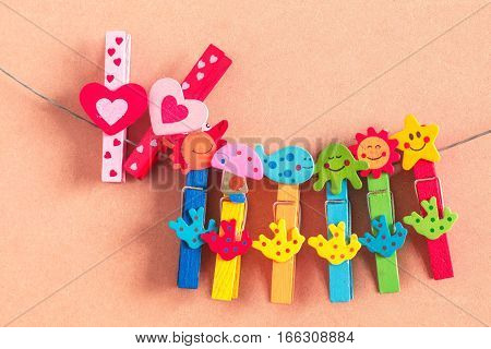 Heart-shaped pin with colorful on wooden floor.