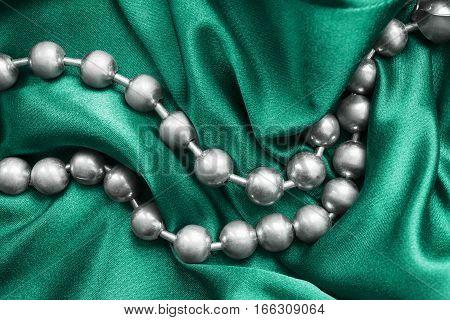Silver metallic beads on crumpled cyan silk closeup