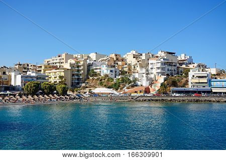AGIOS NIKOLAOS, CRETE - SEPTEMBER 17, 2016 - Tourists relaxing on the beach with apartments to the rear Agios Nikolaos Crete Greece Europe, September 17, 2016.