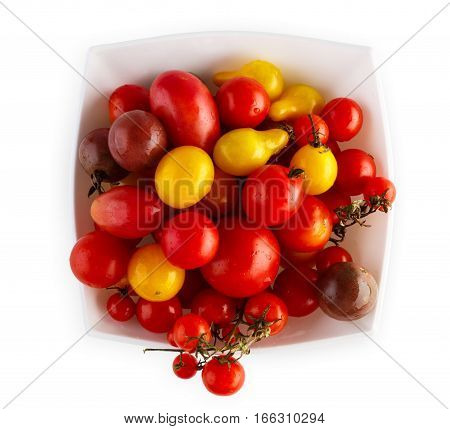 Plenty of Yellow pea, cherry and plum tomato sorts isolated on white background. Closeup pile of ideal sweet vegetables in bowl, healthy natural organic food, top view