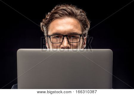 Close-up view of handsome businessman in eyeglasses using laptop on black