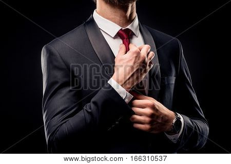 Mid section of businessman in black suit adjusting tie