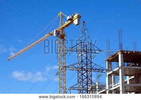 Big yellow hoisting tower crane and top of construction industrial building over cloudless blue sky