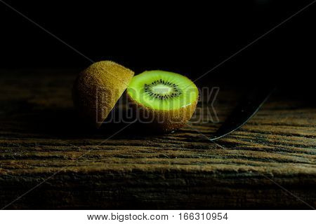 Side of kiwi and knife on wood plate with moody and dark style and background