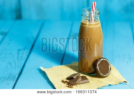 Milk chocolate and chocolate on wood background