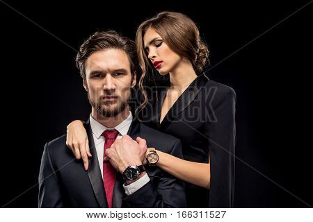 Portrait of beautiful sensual couple hugging and flirting on black