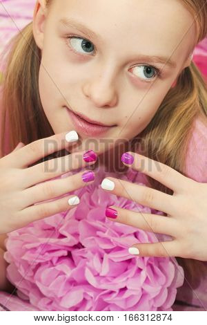 Pink white children's manicure for the girl with the flower.