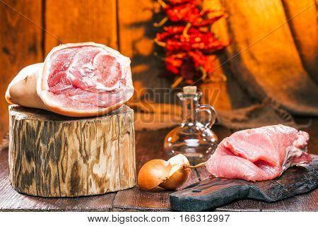 Pork leg and loin. Onion and vinegar bottle. Chili pepper string on wooden wall. Fire light background