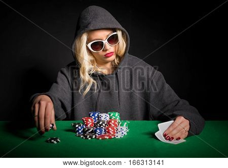 Professional poker player with glasses looking at cards