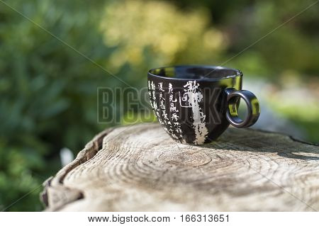 Black japanese tea / coffe cup on woodoutdoor with green background