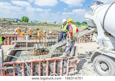 Zrenjanin Vojvodina Serbia - May 29 2015: Workers at building site are pouring concrete in mold from mixer truck.
