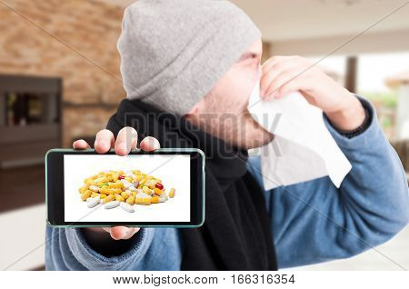 Sick Man Holding Cellphone And Blowing Nose