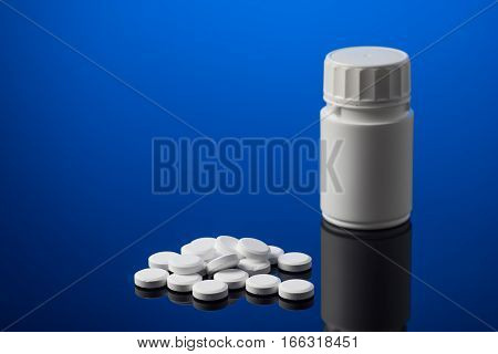 Medicine and white pill box isolated on blue background
