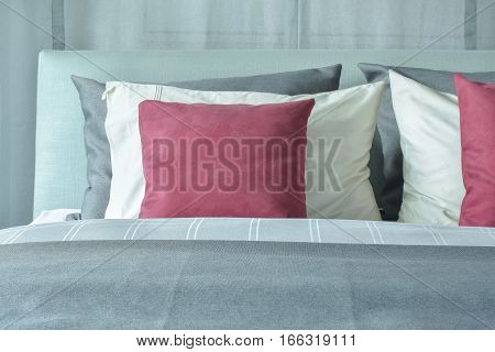 Red Velvet Pillows With White And Gray Pillows Setting On Bed In Gray Color Scheme