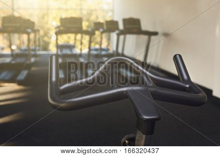 Modern gym interior with equipment. Training exercise bike handlebar in fitness club. Healthy lifestyle concept