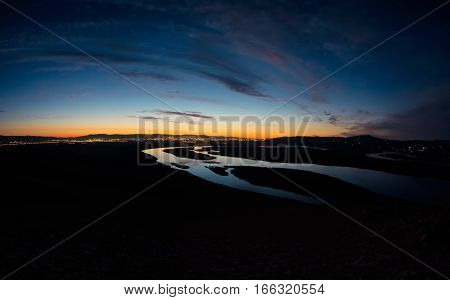 Light of the city at night on a background of a winding river