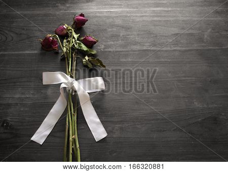 Withered roses with white bow on wooden background