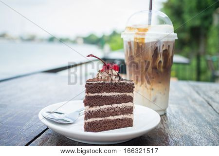 chocolate cake with cherry topping and ice coffee mocha in outdoor cafe. Homemade chocolate cake with chocolate cream stuff.