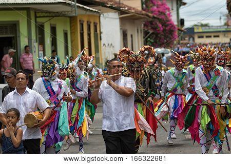 May 25 La Villa de los Santos Panama: men in masks walking on street wearing colourful traditional clothing during Corpus Cristi celebration