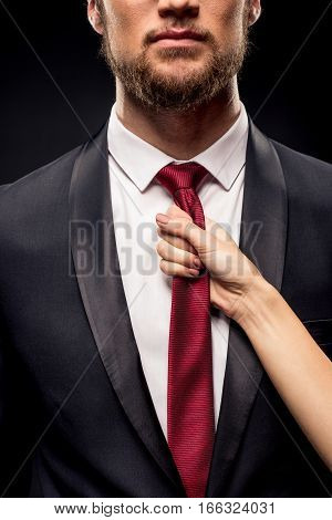 Partial view of woman holding businessman by tie on black