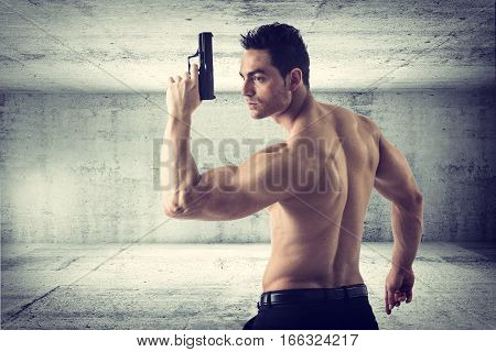 Half body Shot of a Handsome Athletic Man with no Shirt Holding a Handgun While Looking to the Left of the Frame. In cement tunnel