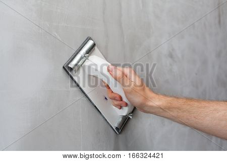 Plasterer erases irregularities on the wall with trowel