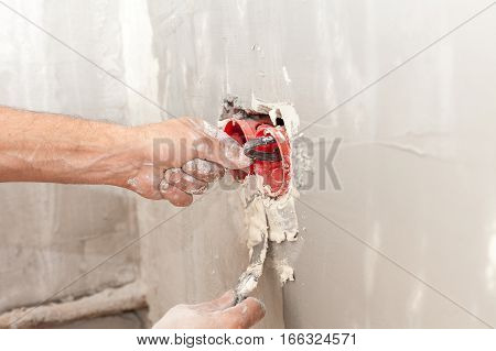 Electrician installing wall power socket plastic electrical junction box with putty knife