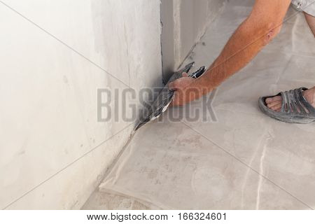 Closeup of repairman hand plastering a wall with putty knife or spatula