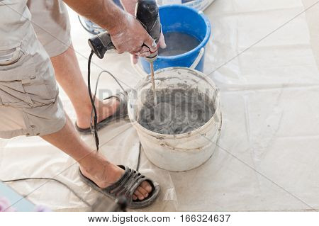 Electric floor heating system installation in new house. Worker use concrete hand mixer to prepare cement