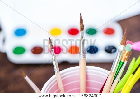 Close-up view of watercolor paints and paintbrushes on wooden table