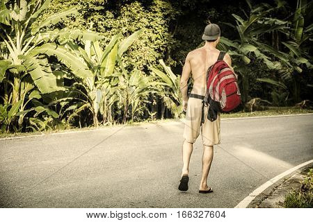 Young muscular topless man with backpack and phone looking away on background of tropical forest, seen from the back