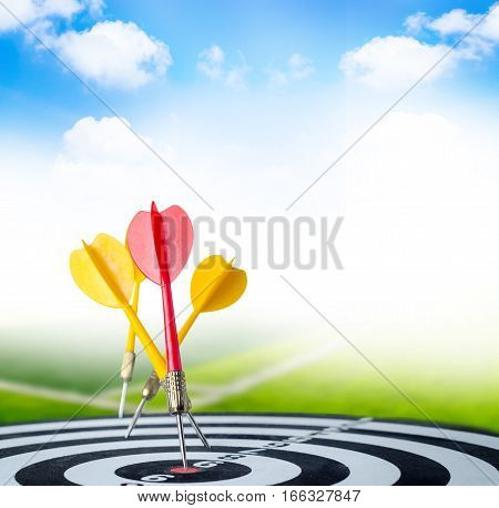 Close up shot red dart arrow on center of dartboard and yellow arrow not hit the target with copyspace metaphor to target success with green field and bluesky background