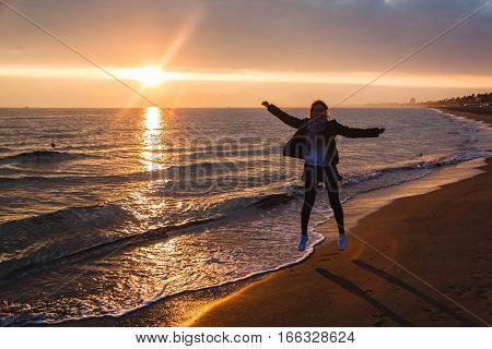Young Girl Is Jumping By The Sea During Sunset In Terracina, Italy