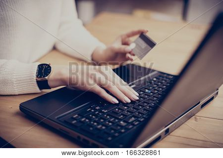 Young businesswoman making online shopping via laptop, typing on keyboard and using her credit card.Horizontal, film effect, blurred background