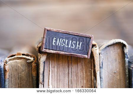 English tag and vintage books on a bookshelf
