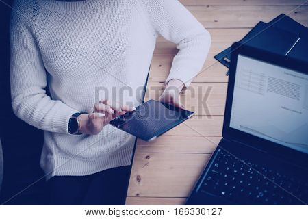 Pensive young woman using modern digital tablet and laptop while sitting at her working place in coworking studio.Horizontal, color filter