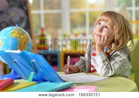 Portrait of cute little boy with lond blond hair does homework