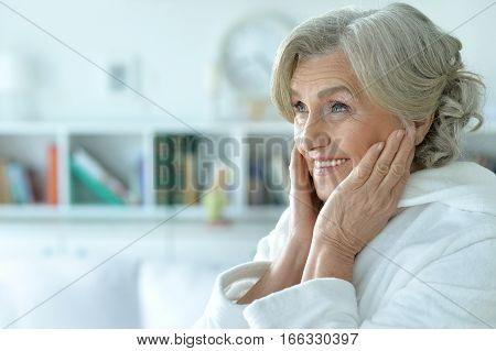 Portrait of happy senior woman with hands on her cheeks