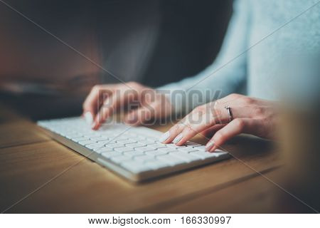 Female hands typing on keyboard.Selective focus on hand.Blurred background.Horizontal