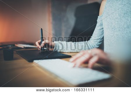 Female hands typing on keyboard.Young woman using digital graphic tablet and drawing pen for new project.Blurred background