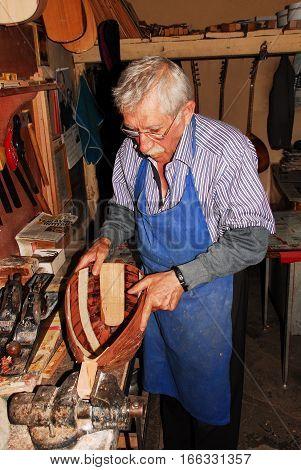 ANKARA, TURKEY - JULY 21, 2011 : A Baglama craftsman carves wood to create Turkish traditional instrument, baglama (saz).