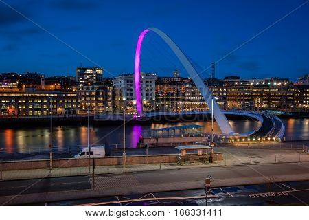 Millennium Bridge over River Tyne at night, on the Quayside in Newcastle on the banks of the River Tyne, and Newcastle upon Tyne skyline beyond