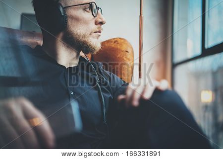 Closeup portrait handsome bearded man in headphones listening to music via mobile phone at modern loft.Guy sitting in vintage chair, holding smartphone hands and relaxing.Horizontal, film effect